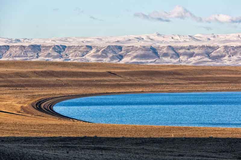 Красивое голубое озеро с заснеженной горы на заднем плане