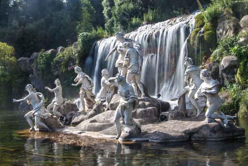 Искусственный водопад и статуя в саду дворца