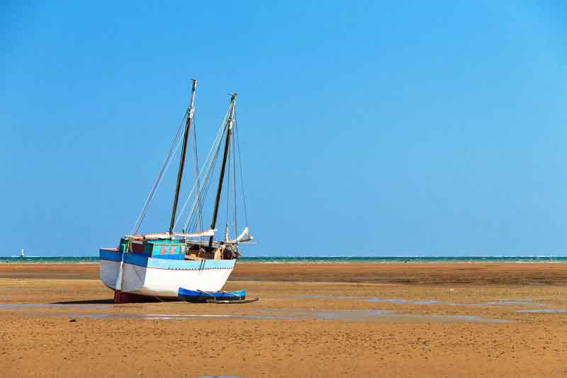 Парусная лодка во время отлива на пляже