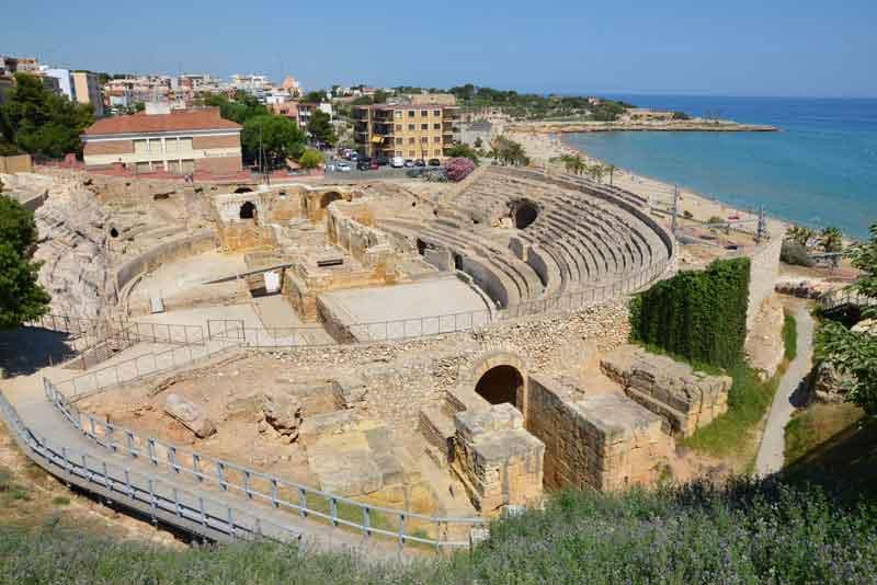 Руины римского амфитеатра на фоне современного города